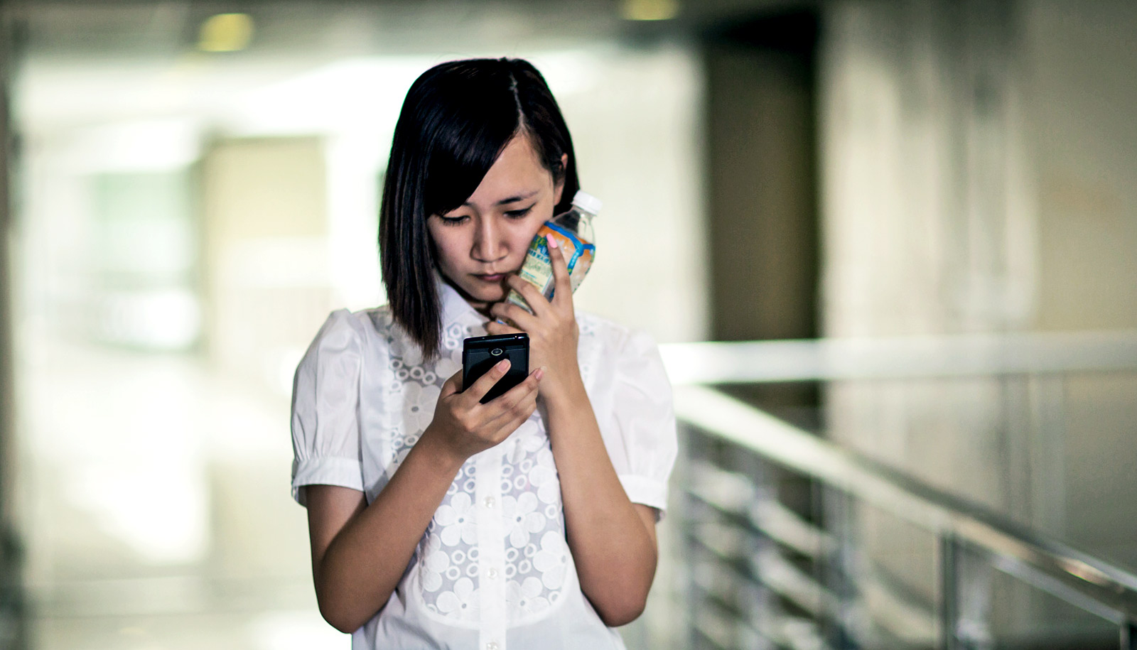 sad young woman looks at phone